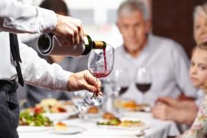 Kellner gießt einen roten Wein ein