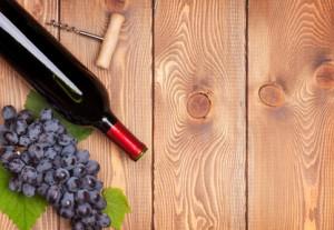 Rotwein-Flasche und Bündel von roten Trauben auf Holztisch