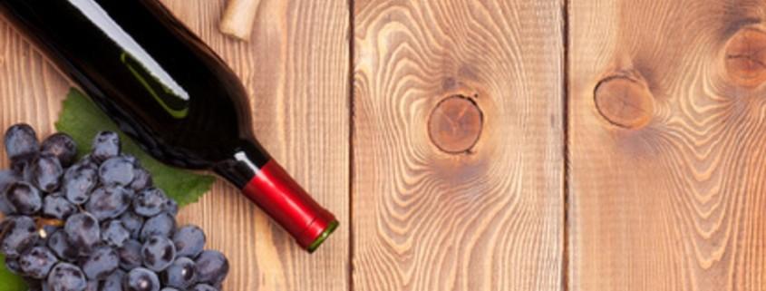Rotweinflasche und Bündel von roten Trauben