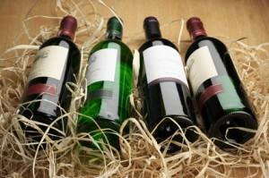 Vier verschiedene Weinflaschen liegen  auf Stroh